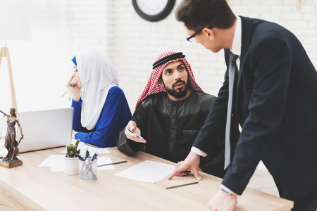 Lawyer in suit in office with arab husband and wife. Man is signing divorce papers. Woman is crying. Stock Photo