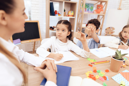Children study letters in class at school. They are sitting at the table. They are helped by an adult teacher. Stock Photo