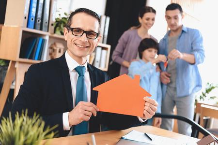 Makler im Anzug am Schreibtisch im Büro sitzen . Makler präsentiert Haussymbol mit Familie im Hintergrund