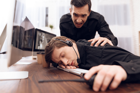 A man guard is sleeping in the workplace. Hes tired. He is sitting in front of monitors in the guard room. His colleague wakes up.