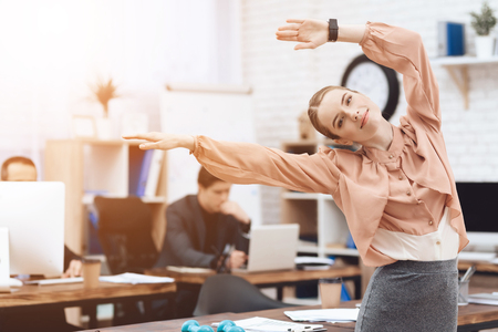 A girl is doing gymnastic exercises at work. She works in a business office. She is tired. Stock Photo