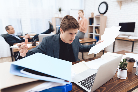The guy is disappointed with the amount of paper work. He works in a business office.
