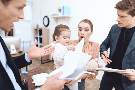 Men have a complaint about a woman who came with her daughter to work. This is a business office. Stock Photo