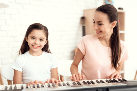 Mom and girl are playing the synthesizer at home. They rest and have fun. Behind them are bookshelves and a white wall.
