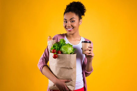 Happy African American girl with groceries isolated on yellow background.