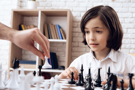 Little boy is learning to play chess. Chess player walks with pawn. Game of chess. Checkmate. Stock Photo