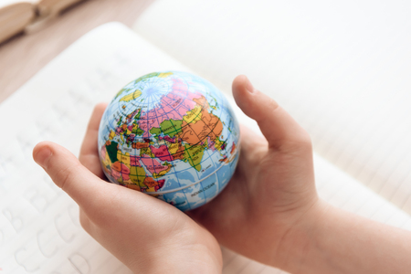 Close up. Child holds small globe in hands. Studies of geography. Self education concept. Stock Photo