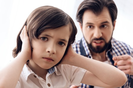 Irate father scolds teenage son which plugs ears. Parenting children concept. Paternity concept.
