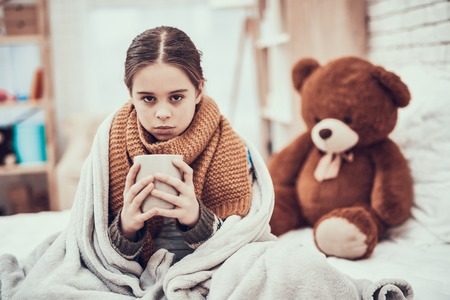 Little girl with cold in scarf and blanket with hot beverage in hands near teddy bear at home. Stok Fotoğraf