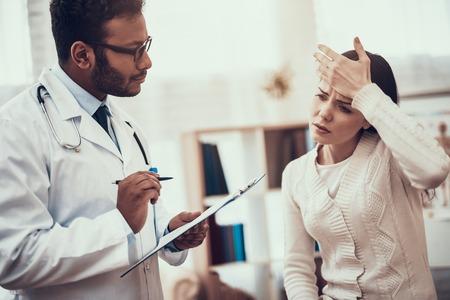 Médico indio en bata blanca viendo pacientes en la oficina. El médico está escuchando los síntomas de la mujer. La mujer tiene fiebre alta.
