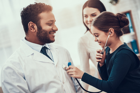 Indian doctor in white gown seeing patients in office. Daughter is using stethoscope on doctor.