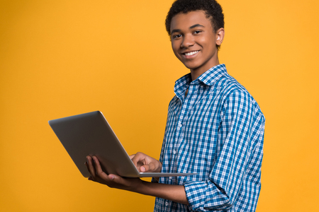 Afro American teenager working with laptop. Isolated on yellow background. Studio portrait.
