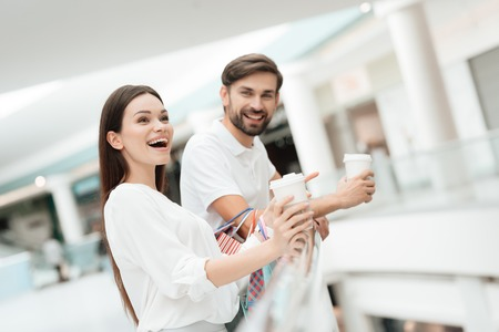 Man and woman with shopping bags in shopping mall. Couple is drinking coffee, laughing.