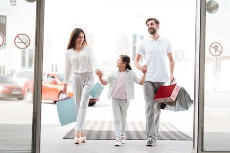 Familia, padre, madre e hija con bolsas de compras están entrando en el centro comercial.