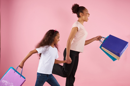 Surprised woman with little daughter runs with paper glossy bags. Shopping and consumerism concept. Isolated on pink background. Studio portrait. Foto de archivo