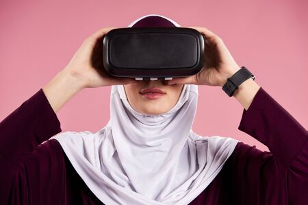 Arab woman puts on virtual reality glasses. Future technology concept. Isolated on pink background.