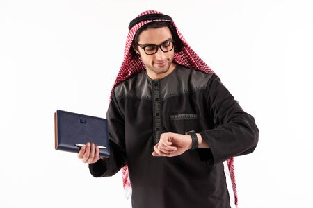 Arab man in keffiyeh with notepad is looking at watch. Isolated on white background.