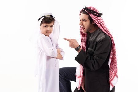 Arabian man in keffiyeh yells at son. Concept of wrong education of children. Parenthood concept. Isolated on white background.