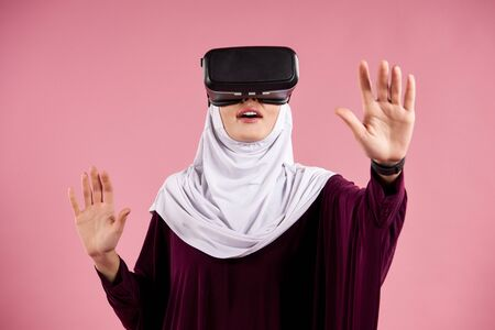 Arab woman in hijab interacts with glasses of virtual reality. Future technology concept. Isolated on pink background.