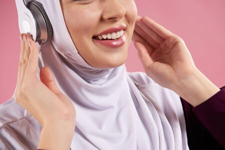 Close up. Arab woman in hijab listens to music on headphones. Isolated on pink background. 스톡 콘텐츠