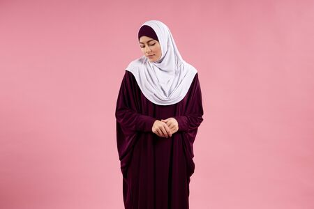 Arabian young woman in hijab is looking down. Expression of innocence. Isolated on pink background. 스톡 콘텐츠