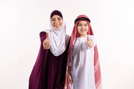 Arab boy and woman in hijab show thumbs up. Isolated on white background. Studio portrait.