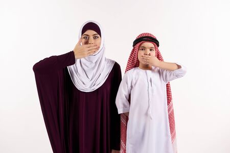 Arab boy and woman in hijab cover mouths with hands. Say no evil. Isolated on white background. 스톡 콘텐츠