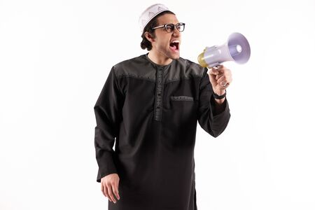 Arab man speaks in megaphone. Announcements concept. Isolated on white background. 스톡 콘텐츠