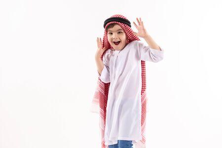 Arabian boy in keffiyeh expresses surprise. Isolated on white background. Studio portrait.
