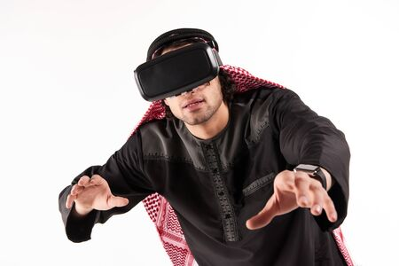 Arab male in keffiyeh tests virtual reality glasses. Future technology concept. Isolated on white background. 스톡 콘텐츠