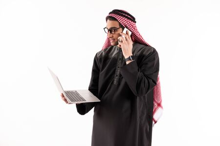 Arab confident businessman in keffiyeh holds laptop with smartphone. Isolated on white background. 스톡 콘텐츠