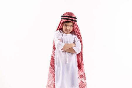 Arab discontented boy in keffiyeh stands with arms crossed. Isolated on white background. Studio portrait.