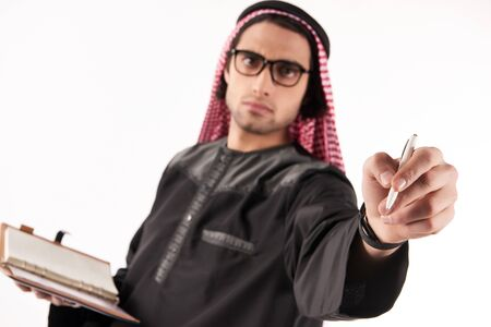 Arab man in keffiyeh makes notes in notebook. Isolated on white background. Studio portrait.