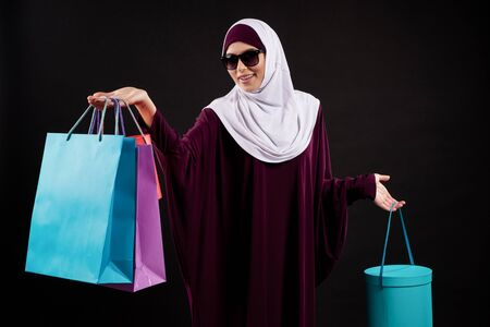 Arab woman in hijab and sunglasses holds paper colored bags. Shopping and consumerism concept. Isolated on black background.