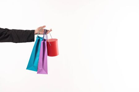 Male stretched hand holds paper bags. Consumerism concept. Isolated on white background. Studio portrait.