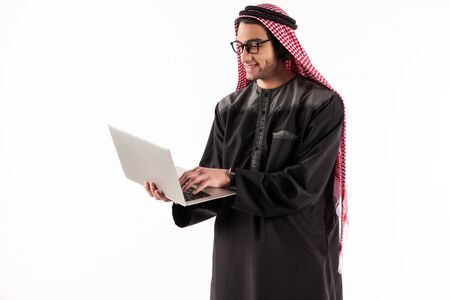 Arab confident businessman in keffiyeh is typing on laptop. Isolated on white background.