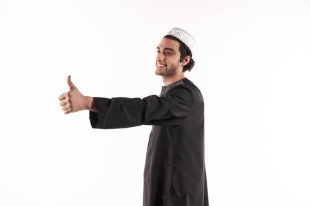 Happy Arab man in ethnic clothes shows thumb up. Isolated on white background. Studio portrait.