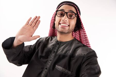 Arab man in keffiyeh makes self portrait with phone. Selfie. Isolated on white background. 스톡 콘텐츠