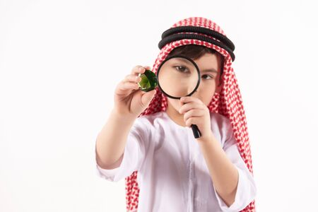 Arabian boy in keffiyeh examines precious stone through magnifying glass. Isolated on white background. Studio portrait.
