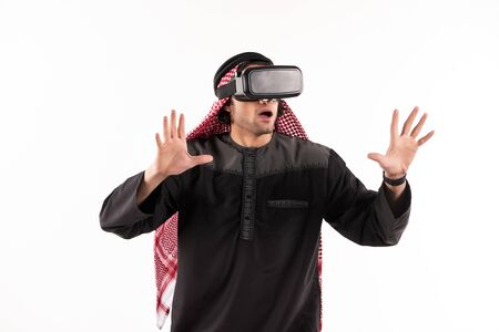 Arab man in virtual reality glasses plays interactive game. Future technology concept. Isolated on white background.