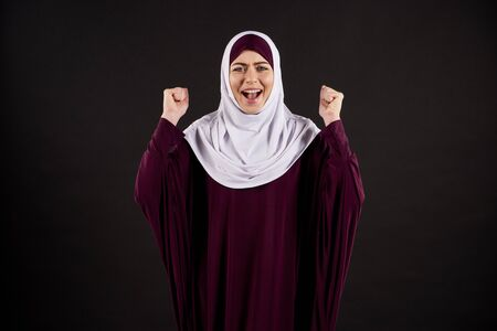 Arab woman in hijab yells with clenched fists. Isolated on black background. Studio portrait.