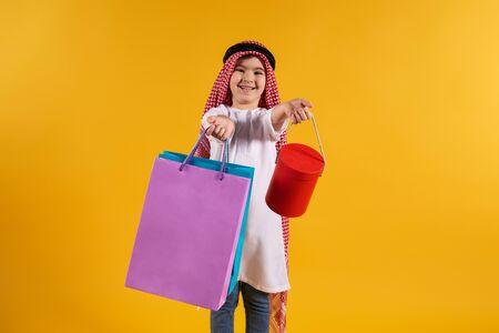 Arab boy in keffiyeh holds paper bags and boxes. Shopping and consumerism concept. Isolated on yellow background.