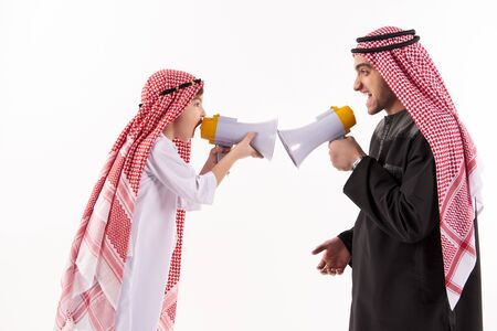 Arab father and little son in national attire shout in megaphones. Isolated on white background. 스톡 콘텐츠