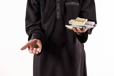 Arab jeweler holds in hands precious stones and bundle of money. Isolated on white background. Studio portrait.