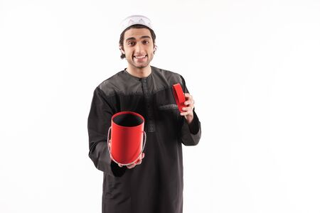 Arab man in ethnic clothes looks in red gift box. Isolated on white background. Studio portrait. 스톡 콘텐츠