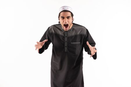 Arab angry man in national clothes screams. Isolated on white background. Studio portrait.