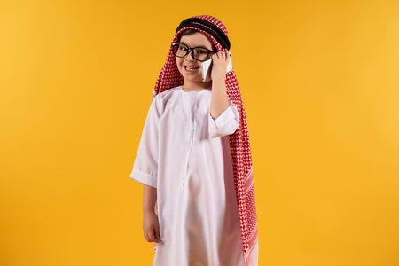 Arab smart boy in kufiya talking on smartphone. Isolated on yellow background. Studio portrait.