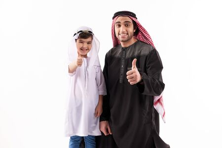 Arab father and son in ethnic clothes show thumbs up. Paternity concept. Isolated on white background. Studio portrait.