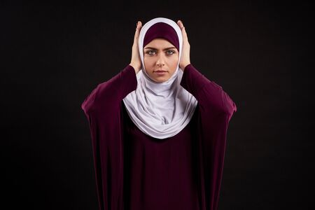 Arab woman in hijab covers ears with hands. Hear no evil. Isolated on black background. 스톡 콘텐츠