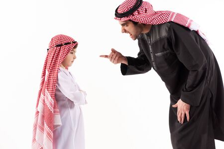 Arab dissatisfied father scolds son in ethnic dress. Upbringing concept. Isolated on white background.